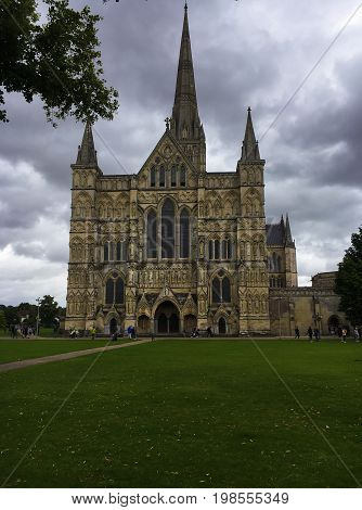 Gothic Salisbury cathedral on cloudy day and the green park