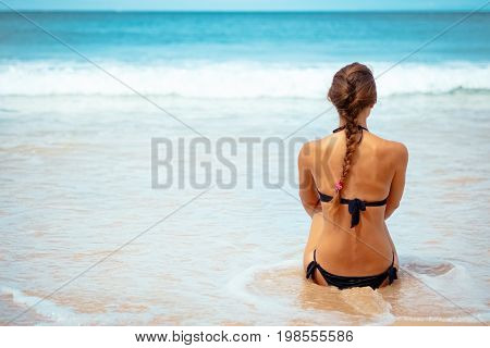 Outdoor summer portrait young elegant pretty fit woman sitting backwards and looking on sea water at tropical beach. Sports girl in bikini enjoy nature paradise at wonderful summer vacation, Thailand.