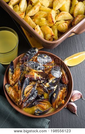 Shellfish mussels in bowl served with baked potato with celery, garlic and lemon. High view angle view