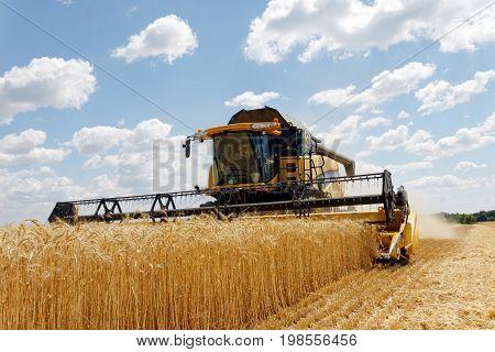 Kharkiv Region Ukraine - July 11 2017: Combine harvest wheat on a field in sunny summer day in Kharkiv Region Ukraine on July 11 2017.
