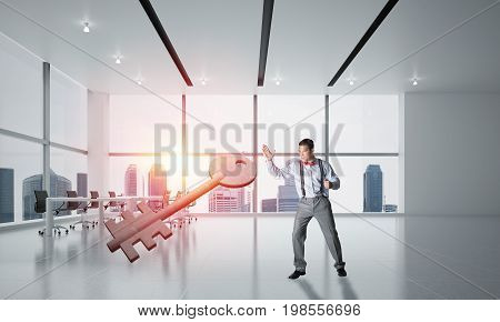 Determined businessman in modern interior breaking with fist stone key figure