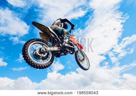 racer on a motorcycle participates in motocross cross-country in flight, jumps and takes off on a springboard against the sky. Concept active extreme rest.