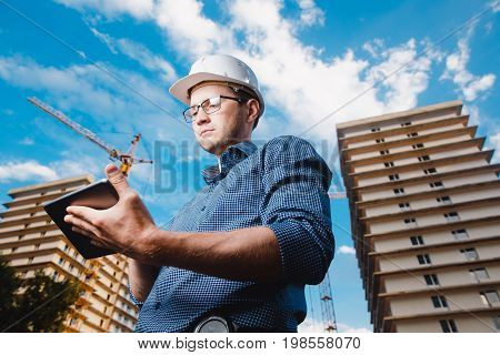 builder is a man in a protective helmet, glasses and a tablet computer in the hands amid a crane, a multi-storey building outside, on the street. Concept construction, business, technology