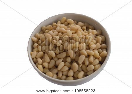 Pine nuts in the white ceramic small bowll isolated on white background