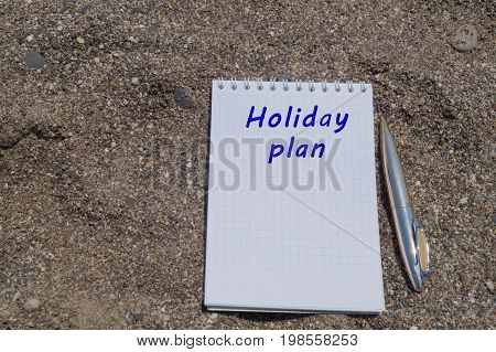 Open white note book on rings with metal ball pen on the sandy beach. Inscription Holiday plan.
