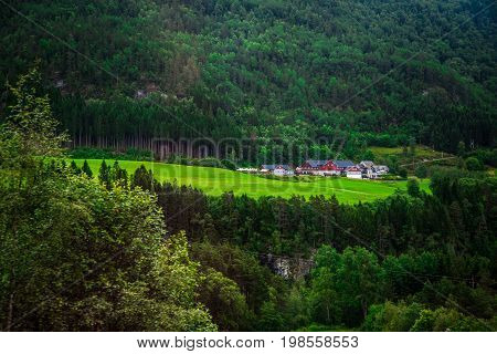 Beautifull green view into a village, with it's fortificated walls in the background. Green background with houses in the middle line