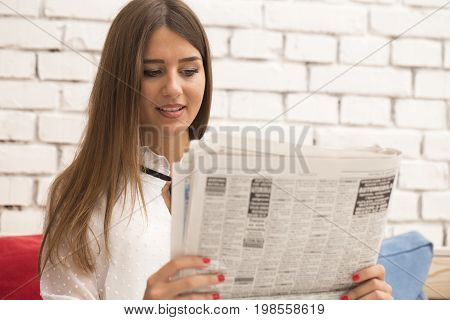 Beautiful young woman leafing through newspapers and looking for an apartment for rent