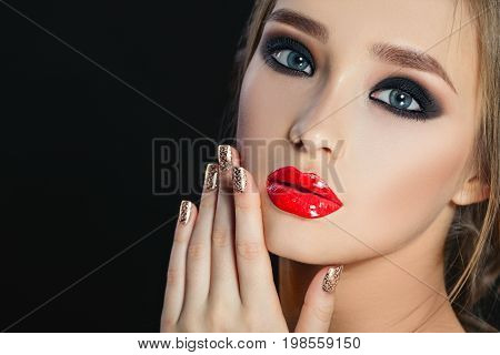 Beauty Woman with Perfect Makeup. Beautiful Professional Holiday Make-up. Red Lips and Nails, perfect eyebrows. Beauty Girl's Face isolated on dark background. Isolated