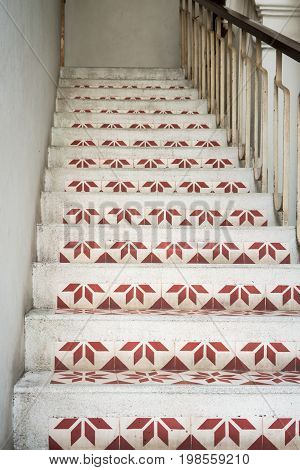 Old stairway in catholic church decorated with geometric pattern tiles in vintage design.