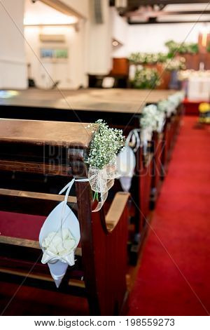 White flower decoration along the pew on red carpet in christian church for religious wedding ceremony. Selective focus