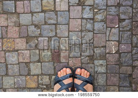 Feet selfie from upper view of a woman traveler in sandal during a tour trip around the world. Tourist take a photo of her own leg