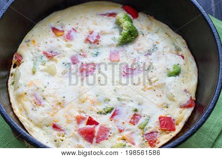 Cooking omelet in a pan ready to serve. With tomatoes red onion goat's cheese and parsley