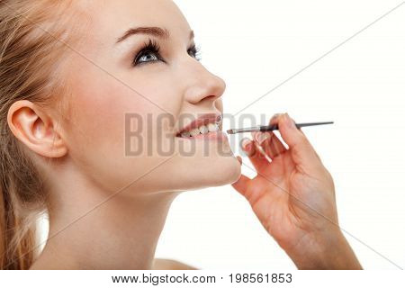 Professional make up applying by artist. Beautiful woman face. Perfect makeup. Makeup detail. Beauty girl with perfect skin