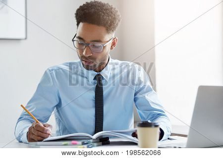Indoor Shot Of Handsome Businessman With Curly Hair, Dressed Formally, Sitting At His Work Place, Wr