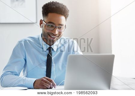 Happy Businessman Wearing Elegant Eyewear And Shirt Watching Video Online While Sitting In Front Of