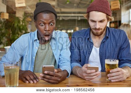 Interracial Men Being Always In Touch, Holding Their Modern Mobile Phones, Typing Messages And Surfi