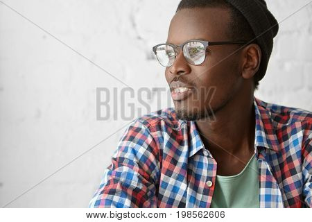 Headshot Of Fashionable Cheerful Afro American Bearded Hipster In Good Mood Having Rest At Cafe. Bla
