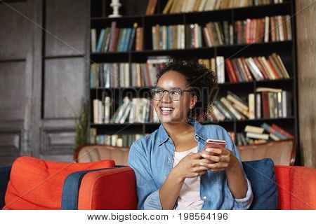Pretty Dark-skinned Woman With Curly Dark Hair, Dressed Casually, Sitting At Sofa In Her Home Readin