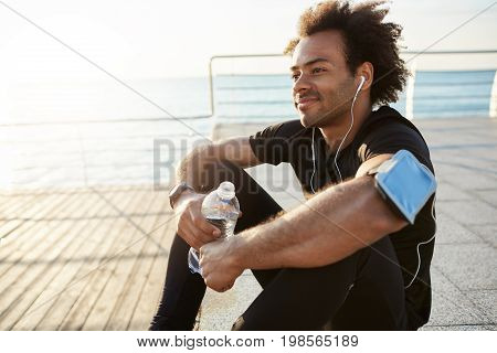 Smiling fit dark-skinned man athlete with bushy hair drinking water out of plastic bottle after hard running workout by the sea. Shot of male runner in black top and leggings resting after successful jogging exercise outdoors. Sportsman in white earphones