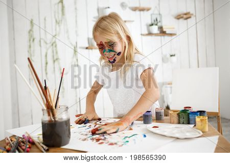 Playful, cute blonde girl having fun by drawing picture with her hands, deeping her palms in different colours and putting them on white sheet of paper. Little laughing girl occupied with drawing in the room filled with light.