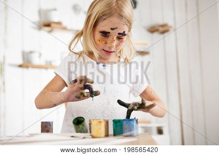 Little blond girl deeping her fingers in paint. European female child occupied with painting, wearing white t-shirt with paint spots on her face. Children and art.