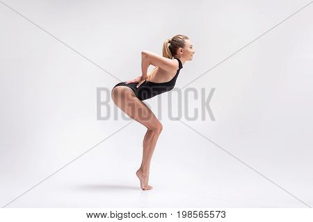 Profile of young happy fit woman in athletic costume standing on toes with bent knees. She is bending forward and smiling