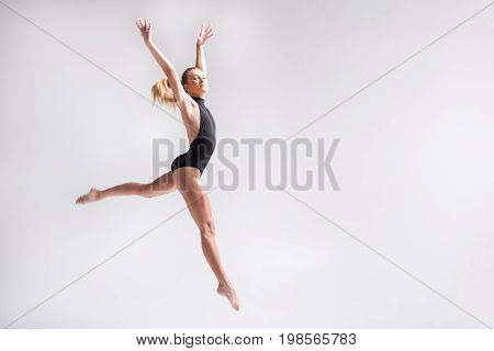Proud young girl is making leap from one leg on another. She is raising hands upwards. Isolated and copy space in right side