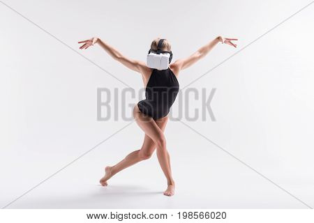 Portrait of young fit girl in vr headset standing barefoot with crossed legs. She is extending arms sideward as bird wings