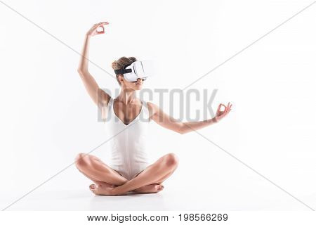 Happy youthful girl in vr headset is sitting on floor in lotus pose. She is extending arms sideward and above her head with smile
