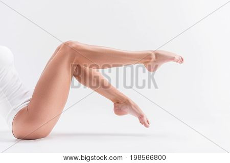 Close up of barefoot legs of young sport woman sitting on floor. She is slightly raising them up and stretching toes