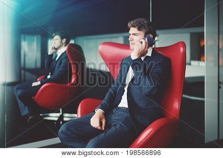 Serious handsome man entrepreneur in formal suit is sitting in red curved armchair in office interior near mirror with reflection of him and window and having work conversation via his smartphone