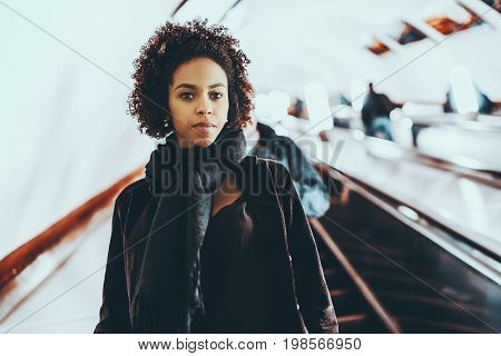 Portrait of young curly serious Brazilian girl with afro hair standing on moving moving staircase of Moscow metro during work day with multiple people and lanterns in blurred background
