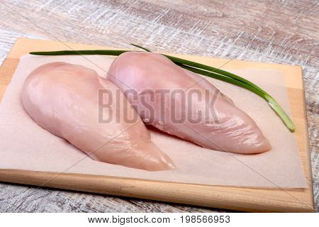 Raw chicken breast fillets and garlic ready for cooking on wooden board.