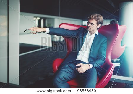 Adult serious man employer in blue formal suit is showing aside by his hand with smartphone while sitting on red elegant armchair in office interior with mirror behind