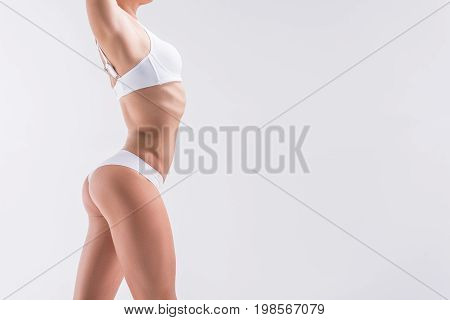 Close up of young slim lady standing in white panties and bra. Copy space in right side. Isolated and focus on hip