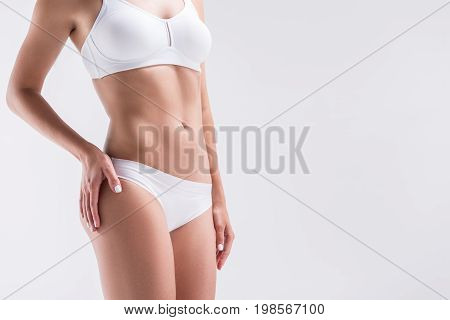 Close up of body of youthful sporty girl standing in cozy set of bra and panties, keeping hand on hip. Copy space in right side. Isolated