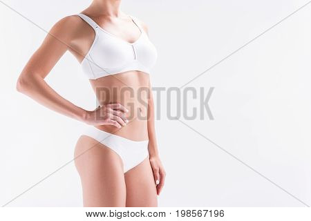 Close up of body of young slim woman standing in white practical underclothing for sport training. Copy space in right side. Isolated