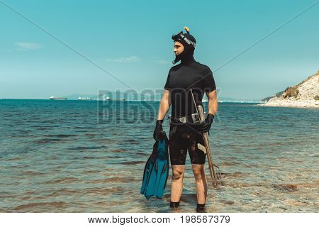 Underwater Hunter Man In Diving Suit With Equipment Goes To Sea In Summer Outdoors
