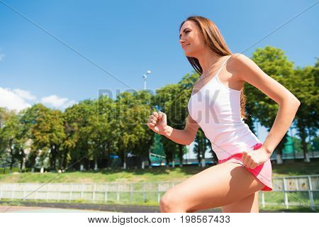 Runner on competition and future success. Girl sunny outdoor on blue sky. Coach or trainer at workout. Sport and healthy fitness. Woman running on arena track.