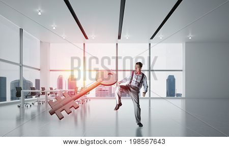 Determined businessman in modern interior breaking with kick stone key figure