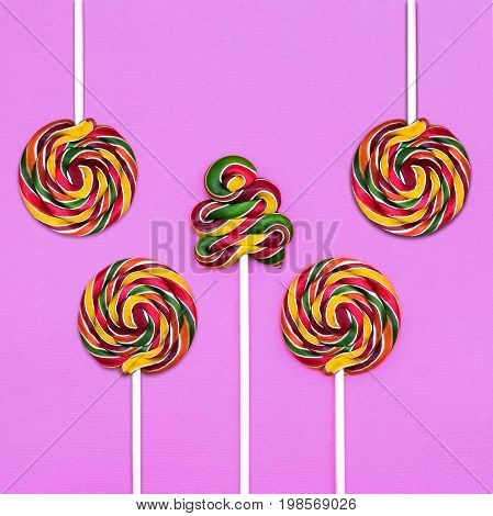 Five multicolored lollipops on a lilac background Four round lollipops and one spiral lollipop Trendy style photo Top view