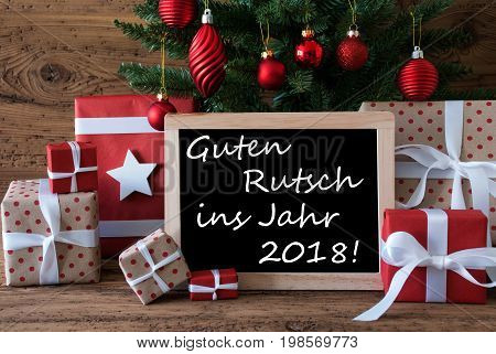 Colorful Card For Seasons Greetings. Christmas Tree With Red Balls. Gifts Or Presents In The Front Of Wooden Background. Chalkboard With German Text Guten Rutsch Ins Jahr 2018 Means Happy New Year