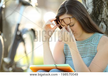 Single student wearing eyeglasses suffering eyestrain while is studying in a park