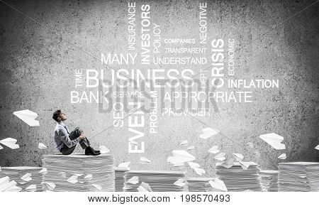 Businessman looking away while sitting on pile of documents among flying paper planes with business-related terms on background. Mixed media.