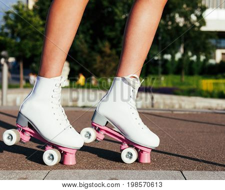 Close-up of women's legs dressed in fashionable vintage roller skates derby quads. Outdoor.