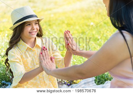 Lets play together. Portrait of excited little girl touching palms on her mom by hands. She is looking at woman with trust and smiling. Family is sitting on grass in summer