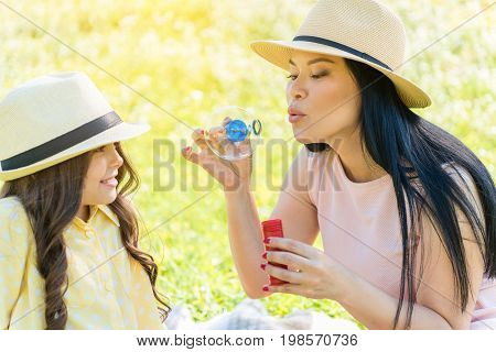 Carefree asian woman is blowing soap bubble with concentration. Her daughter is looking at her with interest and laughing. They are sitting on green grass and relaxing