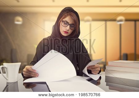 Arab businesswoman revising company financial results. reading document at workplace. Female office worker satisfied with market analysis financial forecast