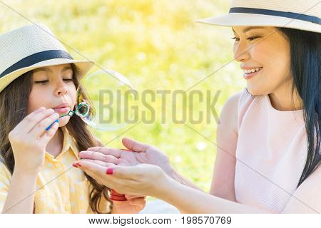 Interested female child is blowing soap bubble with enjoyment. Her mother is trying to catch it by hands and laughing. Family is sitting on meadow