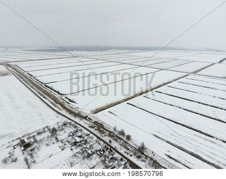 Top View Of A Plowed Field In Winter. A Field Of Wheat In The Snow